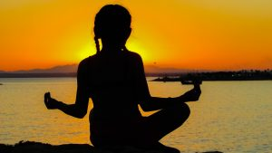 woman meditating sunset